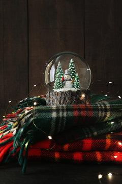 Snow globe on plaid wool blankets