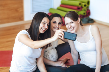 Three pregnant women smiling and photographing themselves by mobile phone