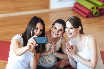 Smiling pregnant women take pictures of themselves on a smartphone in the gym after a workout