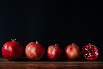 Pomegranates in a Row Against Black Background