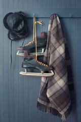 Old men's skates with hat and blanket on hooks