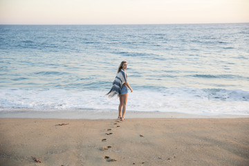 Blonde girl standing on the beach