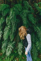 Girl fooling around near a fern