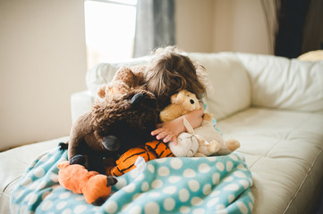 Little girl hiding in her pile of stuffed animals