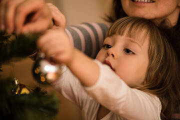 Little girl with her mother decorating xmas tree