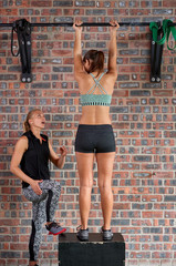 Young sporty woman doing body pull-ups in a gym
