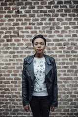Portrait of young African woman against a brick wall