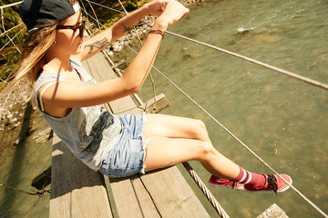 Girl sitting on a hanging bridge over a mountain river in Abkhazia