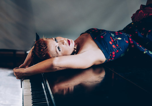 Woman in cherry dress lying on the piano