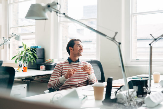 Portrait of happy attractive businessman at meeting at work smiling