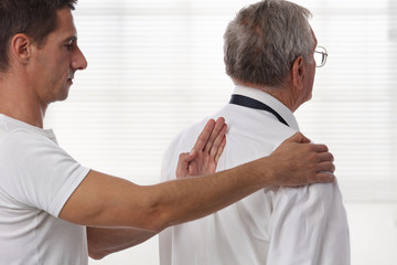 Chiropractic back adjustment. Osteopathy concept. Senior Male patient suffering from back pain and physical therapist