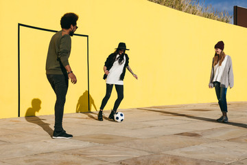 Group of friends having fun playing football in front of a yellow wall.