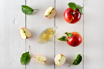 Fresh apples and vinegar on wooden table in kitchen. Concept - healthy food from your garden.