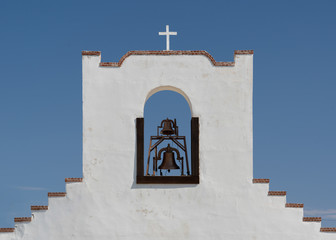 Cross and bell tower of the Socorro Mission in El Paso, Texas