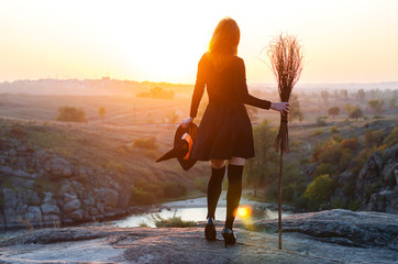 Woman in a witch costume with a broom and hat, a background of halloween.