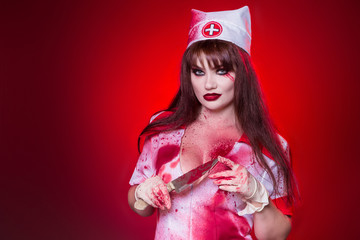 A beautiful, sexy woman, a vampire, a nurse all in blood, holding a knife. Kill the killer, maniac. American, dress for a costume party Halloween.
