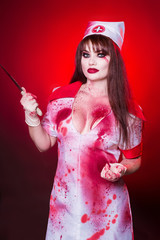 A beautiful, sexy woman, a vampire, a nurse all in blood, holding a knife. Killer, doctor maniac. American, dress for a costume party Halloween.