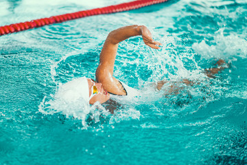 Female swimmer on training in the swimming pool.