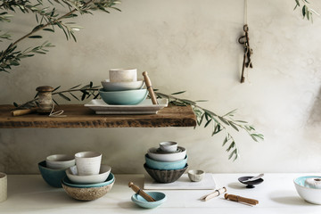 Close-up collection of modern handmade ceramic bowls, plates and cups. Asian statuette