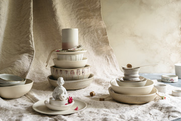 Close-up of handmade ceramic collection bowls, plates and cups. Asian statuette