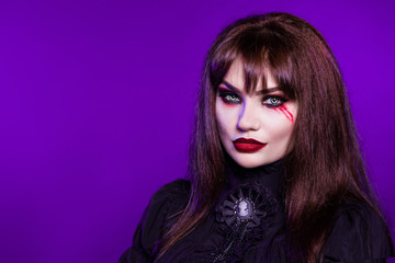 Witch, a vampire in a black gothic dress on a purple background. Portrait. American, dress for a costume party Halloween. Bright makeup