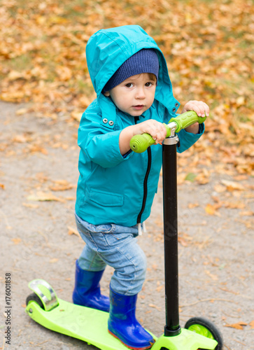 Little Boy In Waterproof Coat And Boots Is Riding Scooter On Yellow