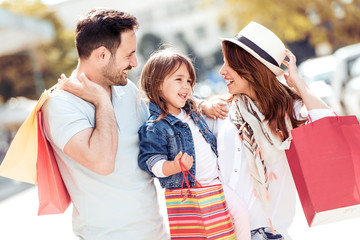 Happy family with little child and shopping bags in city.
