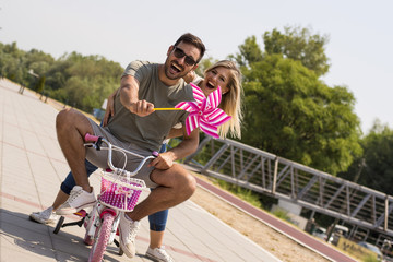 Loving couple having fun while riding bike for kids