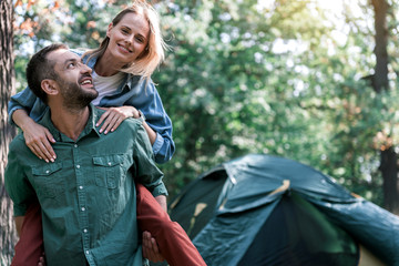 Carefree married couple having fun in forest
