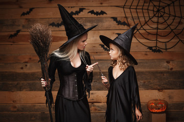 Halloween Concept - stressful witch mother teaching her daughter in witch costumes celebrating Halloween with curved pumpkins over bats and spider web on Wooden studio background.