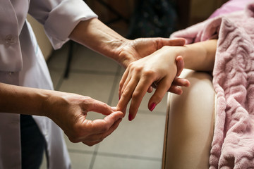 stroking massage of hands close up,Hands massage in the spa salon,Woman in a nail salon receiving a manicure by a beautician.Masseur massaging female palm free space.beating of woman fingers.