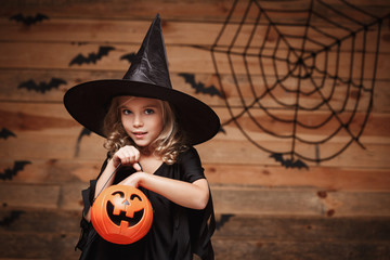 Halloween Witch concept - little caucasian witch child enjoy with halloween candy pumpkin jar. over bat and spider web background. Wall mural
