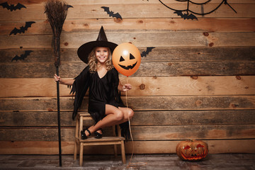 Halloween Witch concept - Full-length shot of little caucasian witch child posing with magic broomstick and balloon over bat and spider web background.