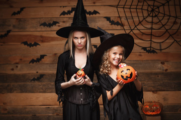Halloween Concept - beautiful caucasian mother with disappointed feeling with happy little daugther enjoy with Halloween candy and sweet over bats and spider web on Wooden studio background.