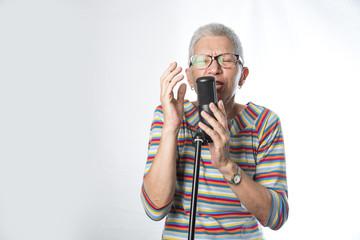Senior elderly woman singing karaoke, expressing her music spirit, having fun, white background