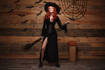 Halloween witch concept - Full-length Happy Halloween red hair Witch holding posing with magic broomstick over old wooden studio background.