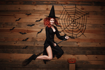 Halloween witch concept - Happy Halloween red hair Witch holding magic broomstick flying gesture over old wooden studio background.