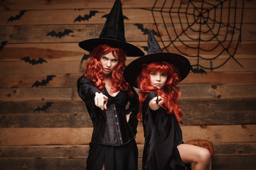 Halloween Concept - Beautiful caucasian mother and her daughter with long red hair in witch costumes and magic wand celebrating Halloween posing.