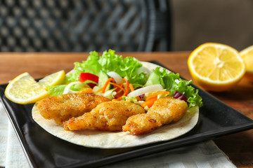 Plate with delicious fish taco on table, closeup