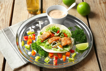Tray with delicious fish taco on wooden table