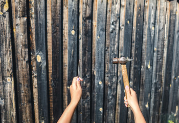 Female hands with a hammer and a nail against the background of old boards