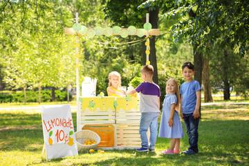 Adorable children standing in line for homemade lemonade outdoors