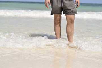 Man with feet in the tropical ocean