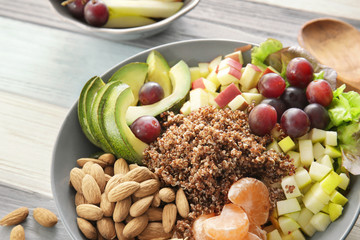 Plate with quinoa, fruits and almonds on wooden background