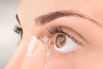Young woman putting contact lens, closeup