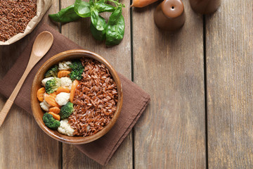 Bowl with tasty brown rice and vegetables on wooden table