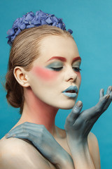 creative fashion beauty portrait of young woman with flower hairstyle. model girl with professional make-up and body art