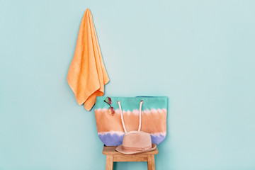 Wall Mural - Composition with apricot towel, handbag and hat on trendy color background
