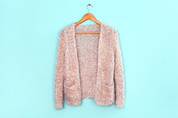 Wall Mural - Apricot cardigan on hanger against trendy color background