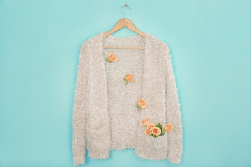 Wall Mural - Warm cardigan decorated with apricot roses against trendy color background